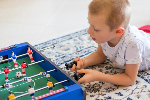 niño jugando futbolín